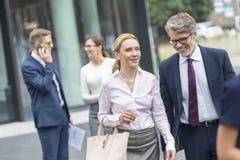 Executivos que falam ao andar contra o escritório imagem de stock royalty free