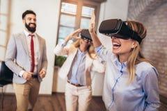 Executivos que fazem o exercício de formação da equipe durante o seminário do desenvolvimento de equipas usando vidros de VR foto de stock