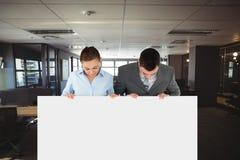 Executivos que guardam o cartão vazio no escritório Foto de Stock Royalty Free