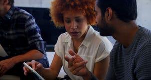 Executivos que interagem ao usar a tabuleta digital video estoque