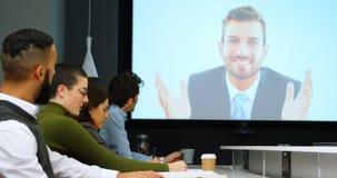 Executivos que interagem com a chamada video na conferência 4k video estoque