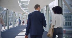 Executivos que interagem um com o otro no corredor no escritório 4k video estoque