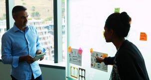 Executivos que leem notas pegajosas na placa de vidro filme