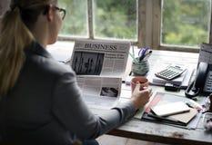 Executivos que leem o jornal no escritório que actualiza a notícia imagem de stock royalty free