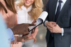 Executivos que leem originais, sócios que discutem o arquivo em papel do contrato no escritório moderno antes de assinar Imagem de Stock