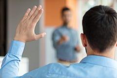 Executivos que levantam lá a mão acima em uma conferência para responder a uma pergunta fotos de stock