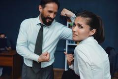 Executivos que mostram os músculos no escritório imagem de stock