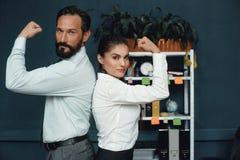 Executivos que mostram os músculos no escritório foto de stock royalty free