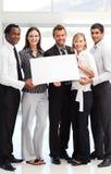Executivos que mostram um cartão branco grande Imagem de Stock