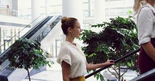 Executivos que movem-se em cima em uma escada rolante no escritório 4k filme