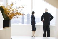 Executivos que olham fora do indicador do escritório. Fotos de Stock