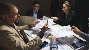 Executivos que planeiam a estratégia para o projeto incorporado no fim do dia de trabalho A equipe do negócio verifica gráficos f filme