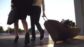 Executivos que saem do aeroporto através da porta de vidro automática com sua bagagem Homem novo e mulher no passeio dos saltos filme