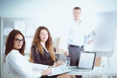 Executivos que sentam-se e que discutem na reunião de negócios, no escritório Ilustração do JPG + do vetor Imagens de Stock Royalty Free