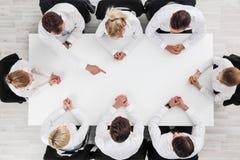 Executivos que sentam-se em torno da tabela vazia Foto de Stock Royalty Free