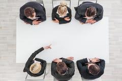 Executivos que sentam-se em torno da tabela vazia Fotos de Stock Royalty Free