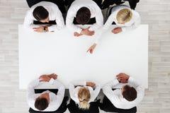 Executivos que sentam-se em torno da tabela vazia Fotografia de Stock