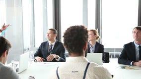 Executivos que sentam-se na tabela quando colega fêmea que dá a apresentação vídeos de arquivo