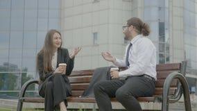 Executivos que sentam-se no banco na frente do corporaçõ que fala e que ri ao guardar copos de café em suas mãos vídeos de arquivo