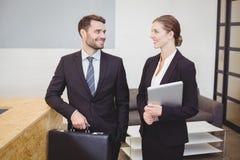 Executivos que sorriem ao falar no escritório fotos de stock royalty free