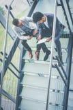 Executivos que têm a conversação em escadas da construção do negócio fotografia de stock