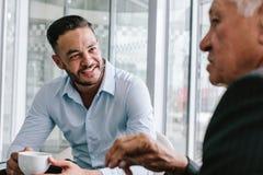 Executivos que têm a conversa ocasional na ruptura de café fotografia de stock royalty free