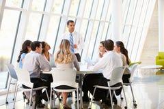 Executivos que têm a reunião da direcção no escritório moderno