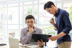 Executivos que trabalham e que discutem no escritório Dois homem U imagens de stock