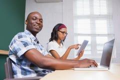 Executivos que trabalham em um portátil e em uma tabuleta Foto de Stock Royalty Free