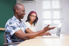 Executivos que trabalham em um portátil e em uma tabuleta Foto de Stock