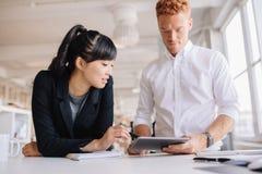 Executivos que trabalham junto na tabuleta digital imagem de stock