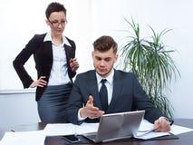 Executivos que trabalham junto no portátil no escritório na mesa Imagem de Stock