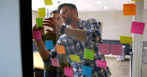 Executivos que trabalham na nota pegajosa na parede de vidro 4k vídeos de arquivo