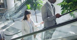 Executivos que usam a escada rolante em um escritório moderno 4k video estoque