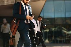Executivos que usam o telefone celular ao andar na rua a de fotografia de stock royalty free