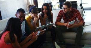 Executivos que usam o telefone celular e a tabuleta digital filme