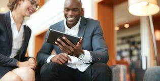 Executivos que usam a tabuleta digital na entrada do hotel imagens de stock royalty free