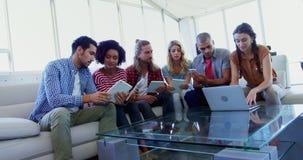 Executivos que usam a tabuleta e o portátil digitais 4k vídeos de arquivo