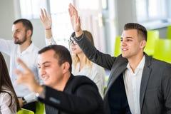 Executivos seguros que levantam as mãos para responder a perguntas do homem de negócio naturalmente fotos de stock