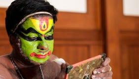 Executor da dança de Katakhali que faz a pintura da cara e a composição na frente do espelho à mão foto de stock