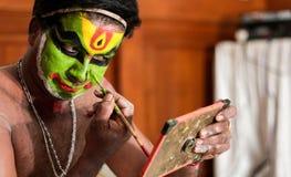 Executor da dança de Katakhali que faz a pintura da cara e a composição na frente do espelho à mão imagem de stock