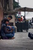 Executor da rua de dois meninos que joga e assento do canto na terra Fotos de Stock