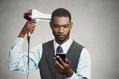 Exekutive, die das intelligente Telefon, sein Haar austrocknend hält Stockfotografie