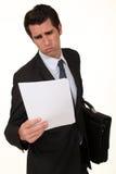 Exekutive, die durch Bericht schaut Lizenzfreie Stockbilder
