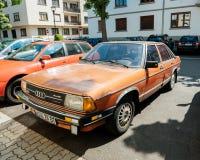 Exekutiveweinlese-Autoparken Audis 100 auf Straße Lizenzfreie Stockfotografie