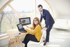 Exekutivgeschäftsfrau und junges behilfliches finanziellbusinessma Stockbild