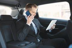 Exekutivgeschäftsmann an der Rückseite des Autos unter Verwendung eines Handys stockfoto