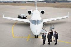 Exekutivgeschäftsteam vor Geschäftsflugzeug sprechend mit pil Lizenzfreie Stockbilder