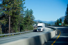 Exelent modern contemporary white semi truck trailers on curvy m Royalty Free Stock Images