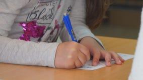 Exellent M?dchen und fauler Junge Das Mädchen schreibt mit Sorgfalt in ein Notizbuch stock video footage